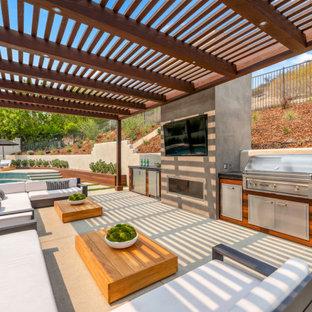 Foto di un grande patio o portico contemporaneo dietro casa con pavimentazioni in cemento e una pergola