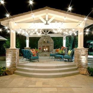 Immagine di un grande patio o portico stile marino dietro casa con un focolare, pavimentazioni in pietra naturale e una pergola