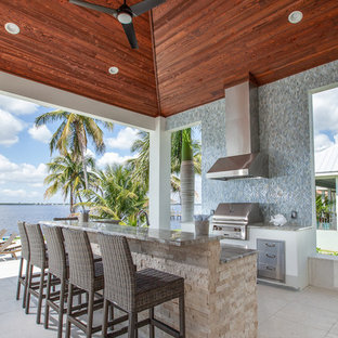 Foto de patio tropical, de tamaño medio, en anexo de casas, con cocina exterior y suelo de baldosas