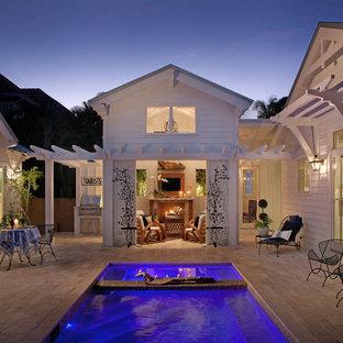 Immagine di un patio o portico tropicale con una pergola e un focolare