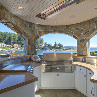 Coastal stone patio photo in Seattle with a roof extension