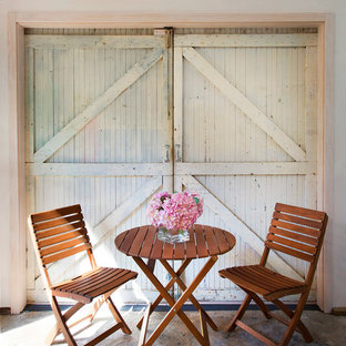Example of a cottage chic patio design in Santa Barbara with a roof extension