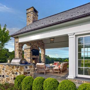 Foto di un patio o portico chic dietro casa con un caminetto, pavimentazioni in pietra naturale e un tetto a sbalzo