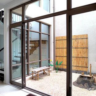 Idee per un grande patio o portico etnico in cortile con ghiaia e un tetto a sbalzo