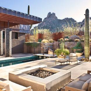 Idee per un ampio patio o portico stile americano dietro casa con pavimentazioni in pietra naturale, nessuna copertura e un focolare