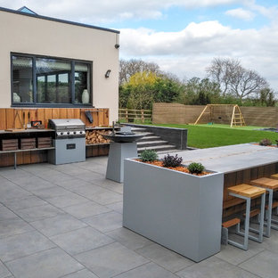 This is an example of a medium sized contemporary back patio in Hertfordshire with an outdoor kitchen, tiled flooring and no cover.