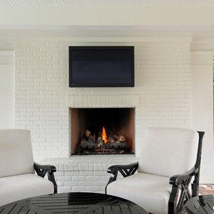 Ispirazione per un patio o portico chic di medie dimensioni e dietro casa con un focolare e pavimentazioni in mattoni