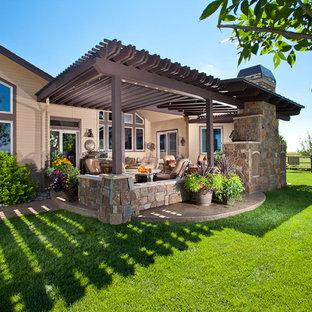 Exemple d'une terrasse chic avec un foyer extérieur et une pergola.
