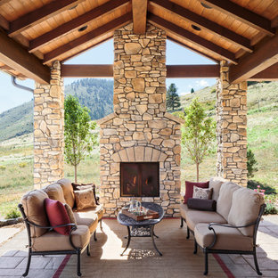Example of a tuscan patio design in Denver with a roof extension and a fireplace