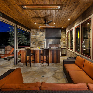 Mid-sized arts and crafts backyard stone patio photo in Denver with a fire pit and a roof extension