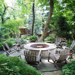 Esempio di un patio o portico mediterraneo dietro casa con un focolare, lastre di cemento e nessuna copertura