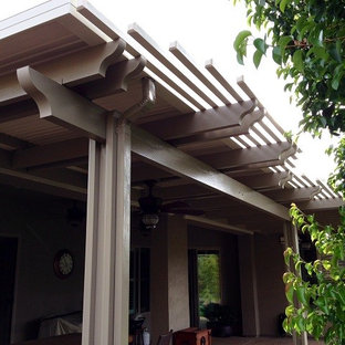 This is an example of a medium sized back patio in Sacramento with concrete slabs and an awning.