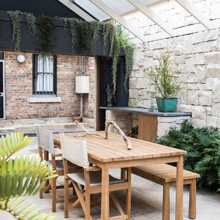 Design ideas for a small country courtyard patio in Sydney with natural stone pavers and a pergola.
