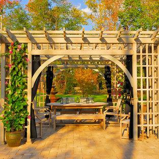 Immagine di un ampio patio o portico tradizionale dietro casa con una pergola e pavimentazioni in pietra naturale