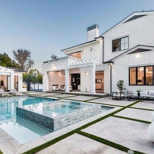 Ispirazione per un grande patio o portico minimal dietro casa con un caminetto, pavimentazioni in cemento e un gazebo o capanno