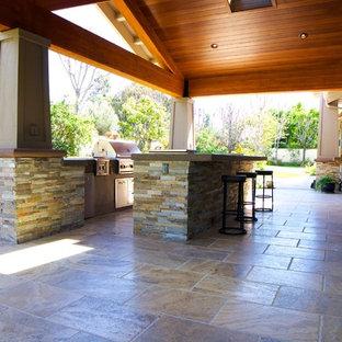 Idee per un grande patio o portico stile americano dietro casa con piastrelle e un tetto a sbalzo