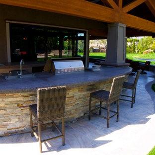 Ispirazione per un grande patio o portico stile americano dietro casa con piastrelle e un tetto a sbalzo