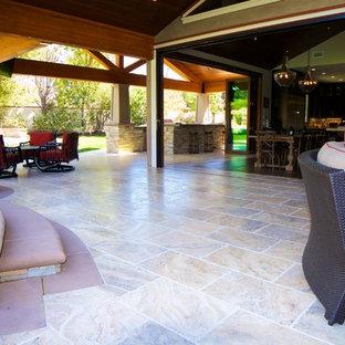 Esempio di un grande patio o portico stile americano dietro casa con piastrelle e un tetto a sbalzo