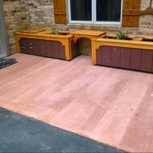 Esempio di un patio o portico tradizionale davanti casa con lastre di cemento