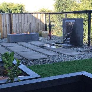 Ispirazione per un grande patio o portico minimal dietro casa con un focolare, lastre di cemento e nessuna copertura