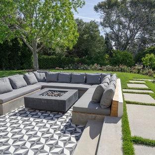Immagine di un grande patio o portico design dietro casa con un focolare, piastrelle e nessuna copertura