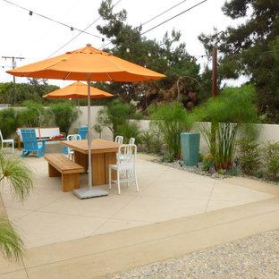 Esempio di un piccolo patio o portico costiero dietro casa con un focolare e lastre di cemento