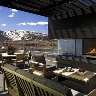 Cette image montre une grande terrasse arrière design avec un foyer extérieur et une pergola.