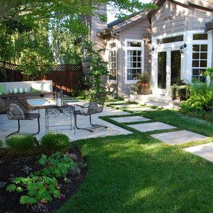 Idee per un patio o portico tradizionale di medie dimensioni e dietro casa con un focolare e pavimentazioni in cemento