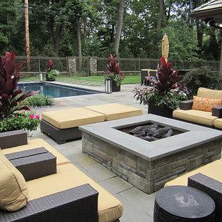 Immagine di un ampio patio o portico minimal dietro casa con un focolare, piastrelle e nessuna copertura