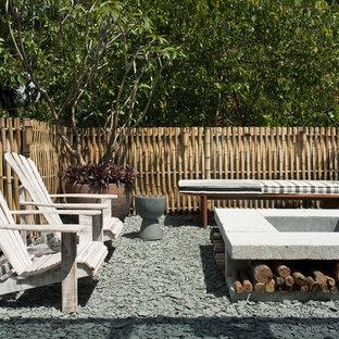 Ispirazione per un patio o portico tropicale con un focolare e nessuna copertura