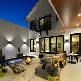 Idee per un patio o portico minimal dietro casa con fontane, un tetto a sbalzo e lastre di cemento
