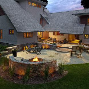 Immagine di un grande patio o portico stile americano dietro casa con un focolare e lastre di cemento
