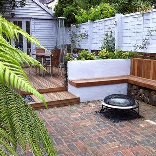 Immagine di un patio o portico minimal con pavimentazioni in mattoni e un focolare