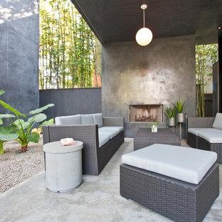 Idee per un patio o portico contemporaneo di medie dimensioni e in cortile con un focolare, lastre di cemento e un tetto a sbalzo