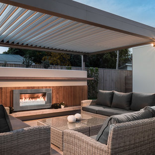 Contemporary backyard patio in Christchurch with a pergola and with fireplace.