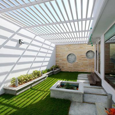 Patio - contemporary concrete paver patio idea in Other with a pergola