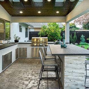 Cette image montre une grande terrasse avec une cuisine extérieure arrière design avec une dalle de béton et une extension de toiture.