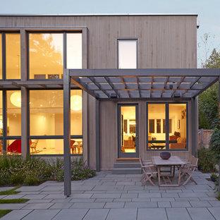 Inspiration for a contemporary concrete paver patio remodel in Boston with a pergola