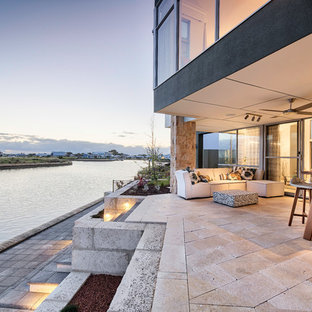 Design ideas for a contemporary backyard patio in Perth with natural stone pavers and a roof extension.