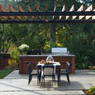 Esempio di un patio o portico country di medie dimensioni e dietro casa con pavimentazioni in cemento e una pergola