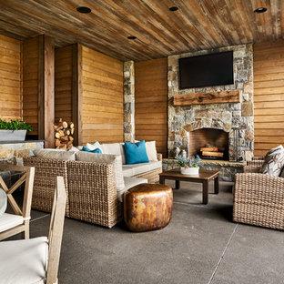 Foto di un grande patio o portico country dietro casa con cemento stampato e un tetto a sbalzo
