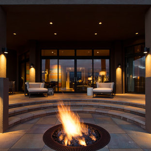 Trendy patio photo in Albuquerque with a fire pit and a roof extension