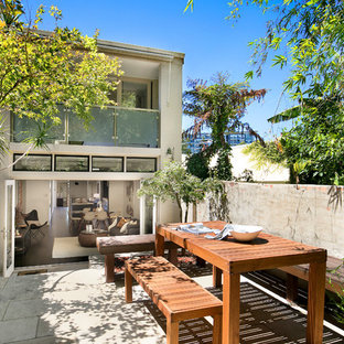 This is an example of a contemporary courtyard patio in Sydney with no cover and tile.