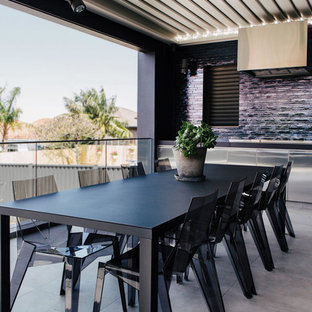 Contemporary backyard patio in Sydney with an outdoor kitchen, concrete pavers and a roof extension.