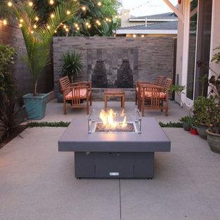 Immagine di un piccolo patio o portico minimal dietro casa con un focolare, lastre di cemento e nessuna copertura