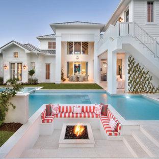 Idee per un ampio patio o portico stile marino dietro casa con un focolare