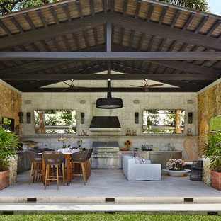 Mediterranean patio in Chicago with an outdoor kitchen, natural stone paving and a roof extension.
