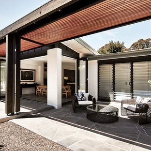 Inspiration for a contemporary backyard patio in Sydney with natural stone pavers and no cover.