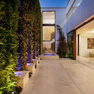 Patio fountain - mid-sized contemporary backyard tile patio fountain idea in Orange County with no cover