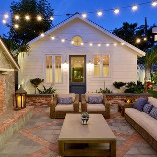 Idee per un piccolo patio o portico costiero dietro casa con un focolare, piastrelle e nessuna copertura